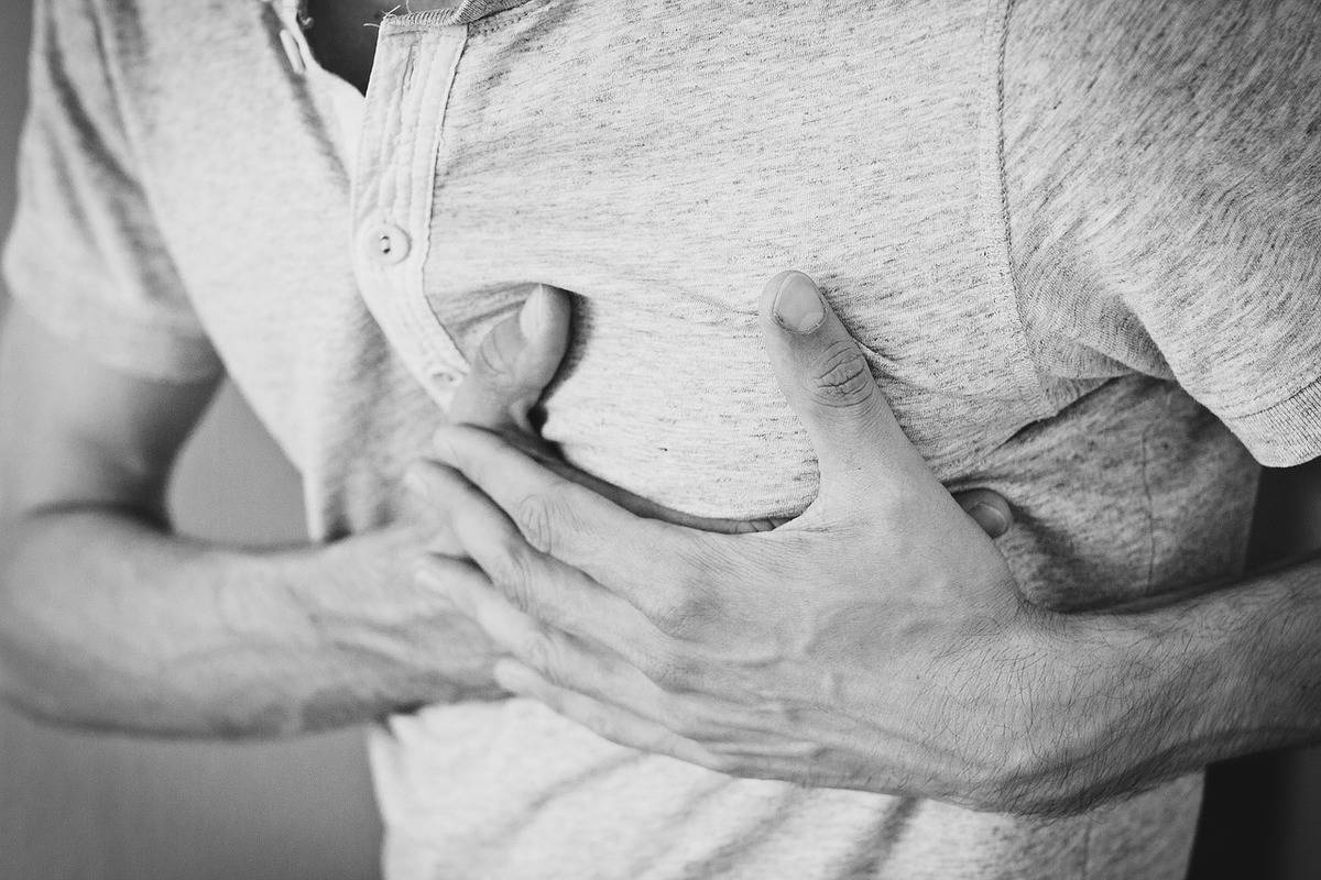 A man clutches his chest in pain.