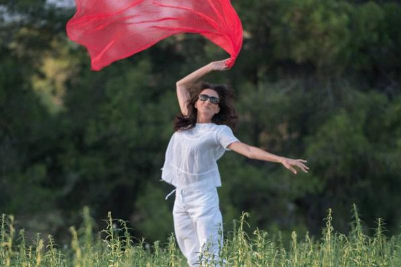 A woman waves around a red cloth with elation.