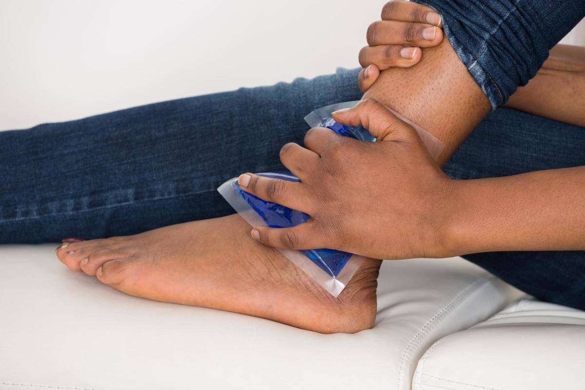 A woman presses an ice pack against her ankle.