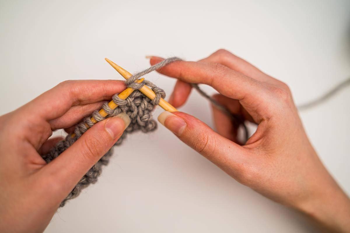 A woman knits.