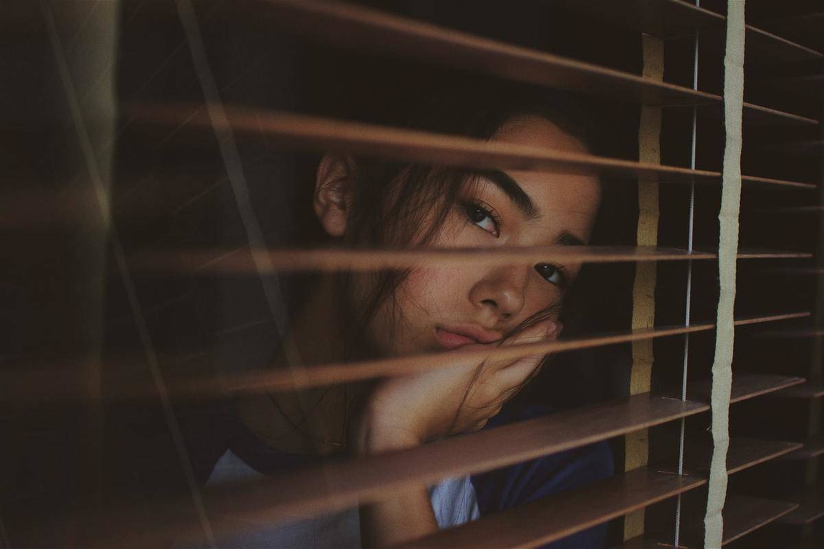 A woman looks out the window while bored.