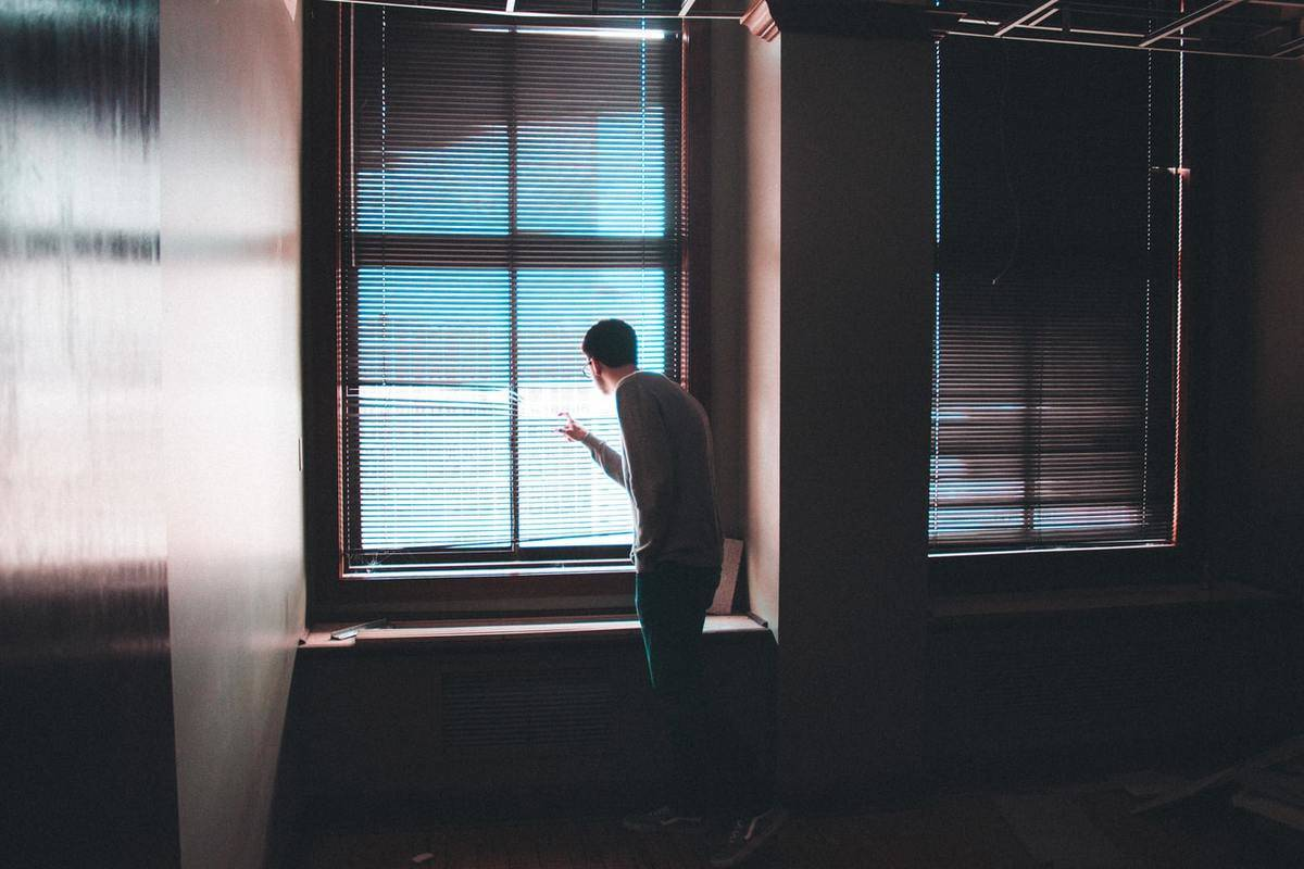 A man peeks through the window blinds.
