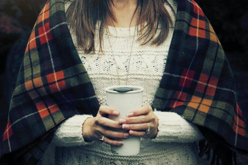 A woman holds a white travel mug.