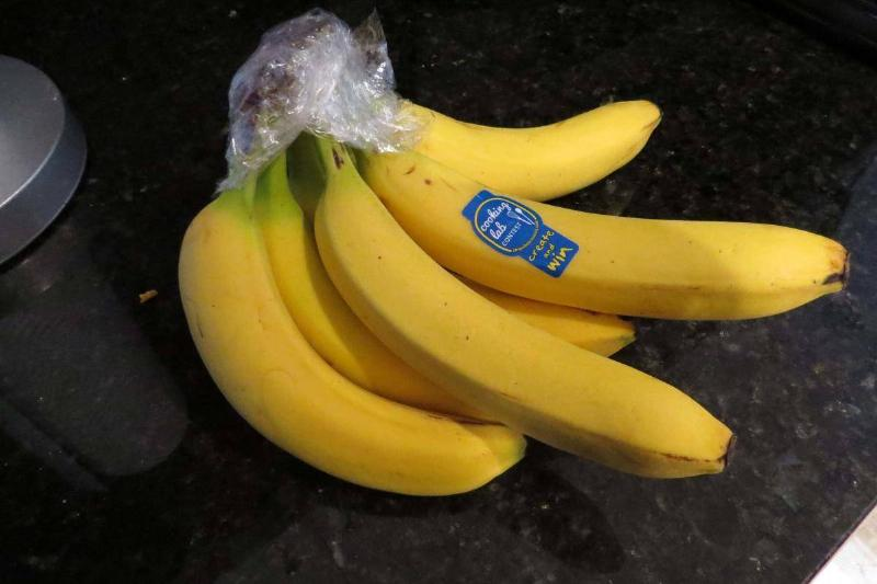 The stem of a bundle of bananas is covered in plastic wrap.