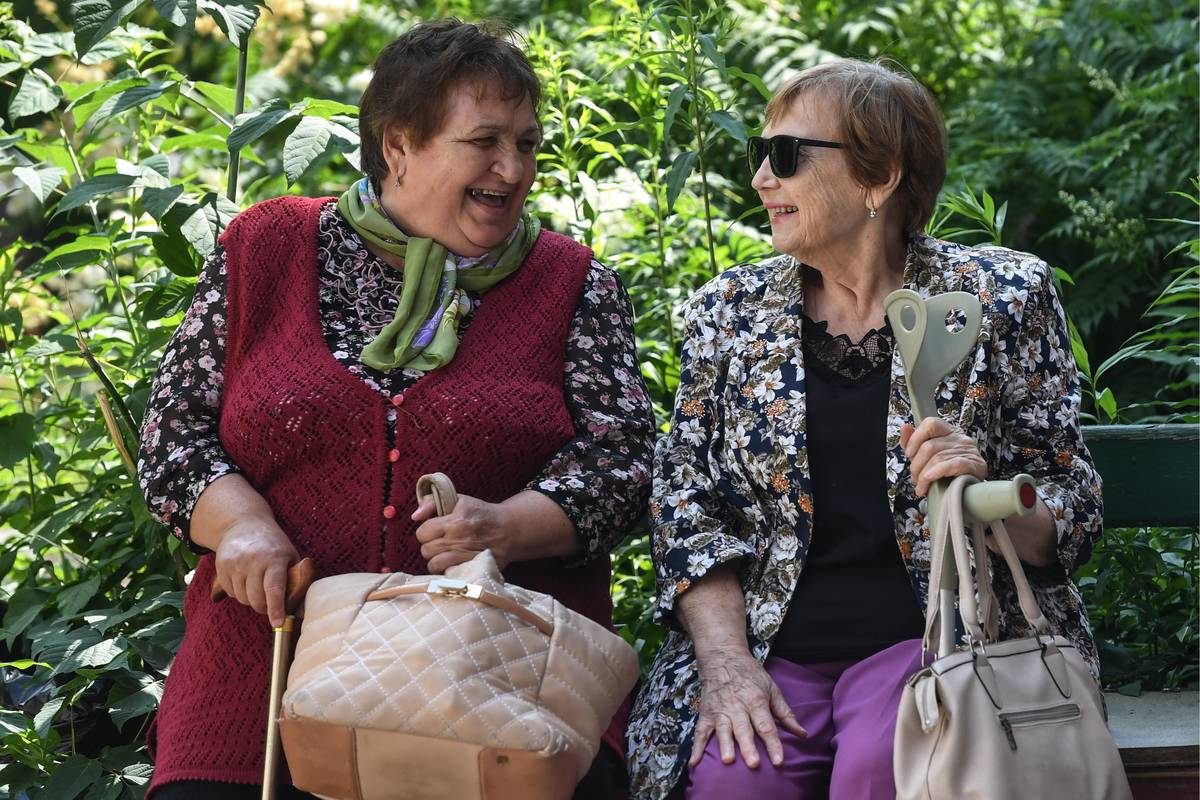 Two senior women talk while sitting on a park bench.