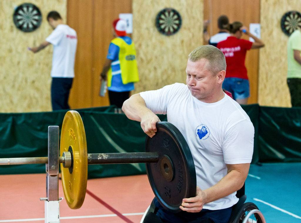 A man loads a barbell with weight plates.