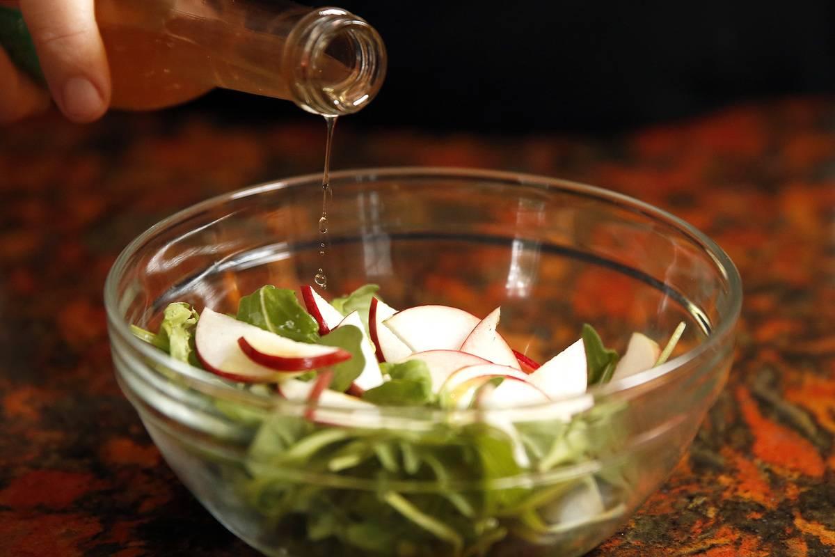 A cook splashes apple cider vinegar onto a salad.