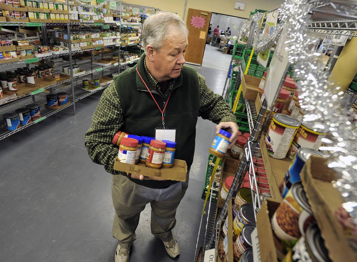 A man stocks the shelves with jars of peanut butter.