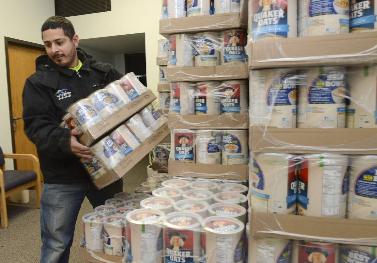 A man lifts a package of raw oatmeal containers.