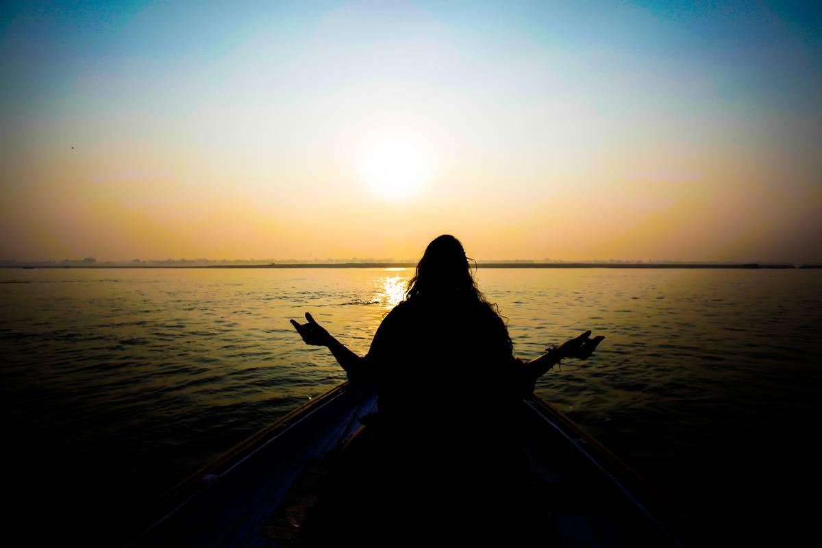A woman meditates on a beach at sunset.