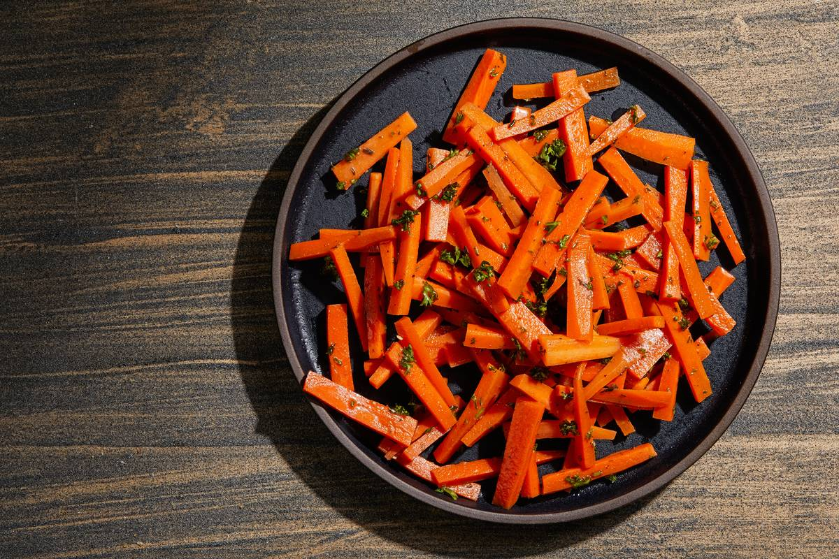 Sliced marinated carrots sit on a black circular tray.