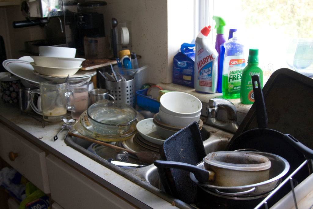 A sink is overflowing with dirty dishes.
