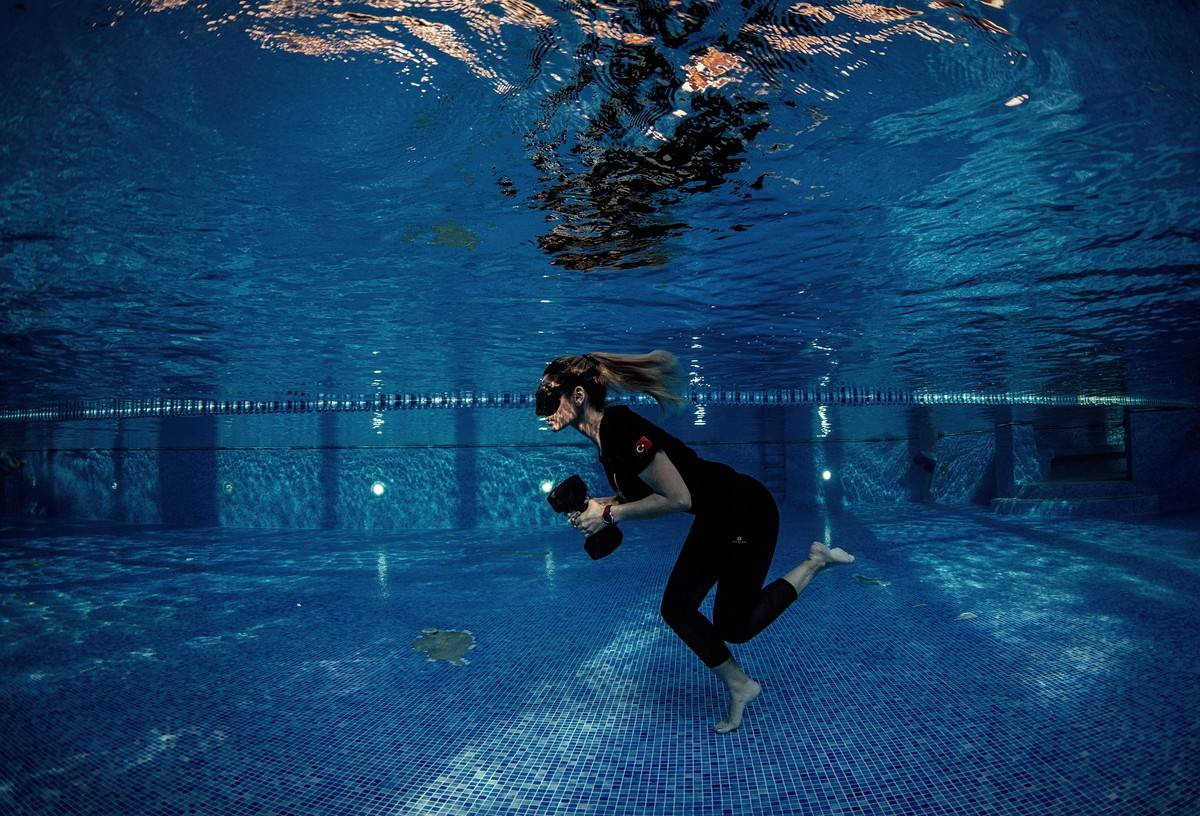 A woman runs and lifts weights underwater.