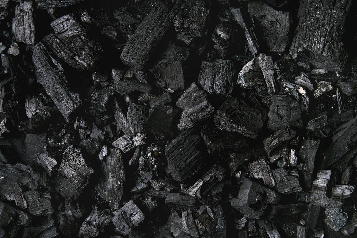 A photo shows a pile of charcoal pieces.