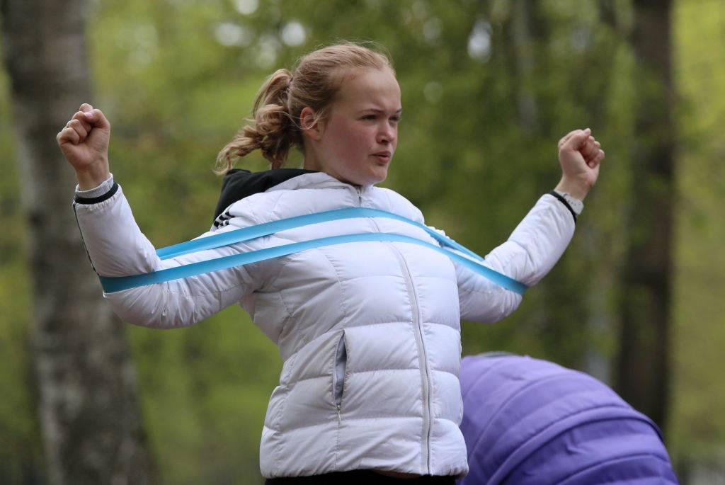A woman exercises with a resistance band.