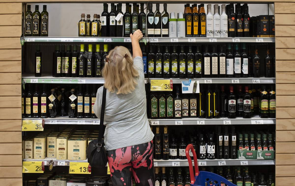 A customer picks up a bottle of Spanish extra-virgin olive oil at a supermarket.
