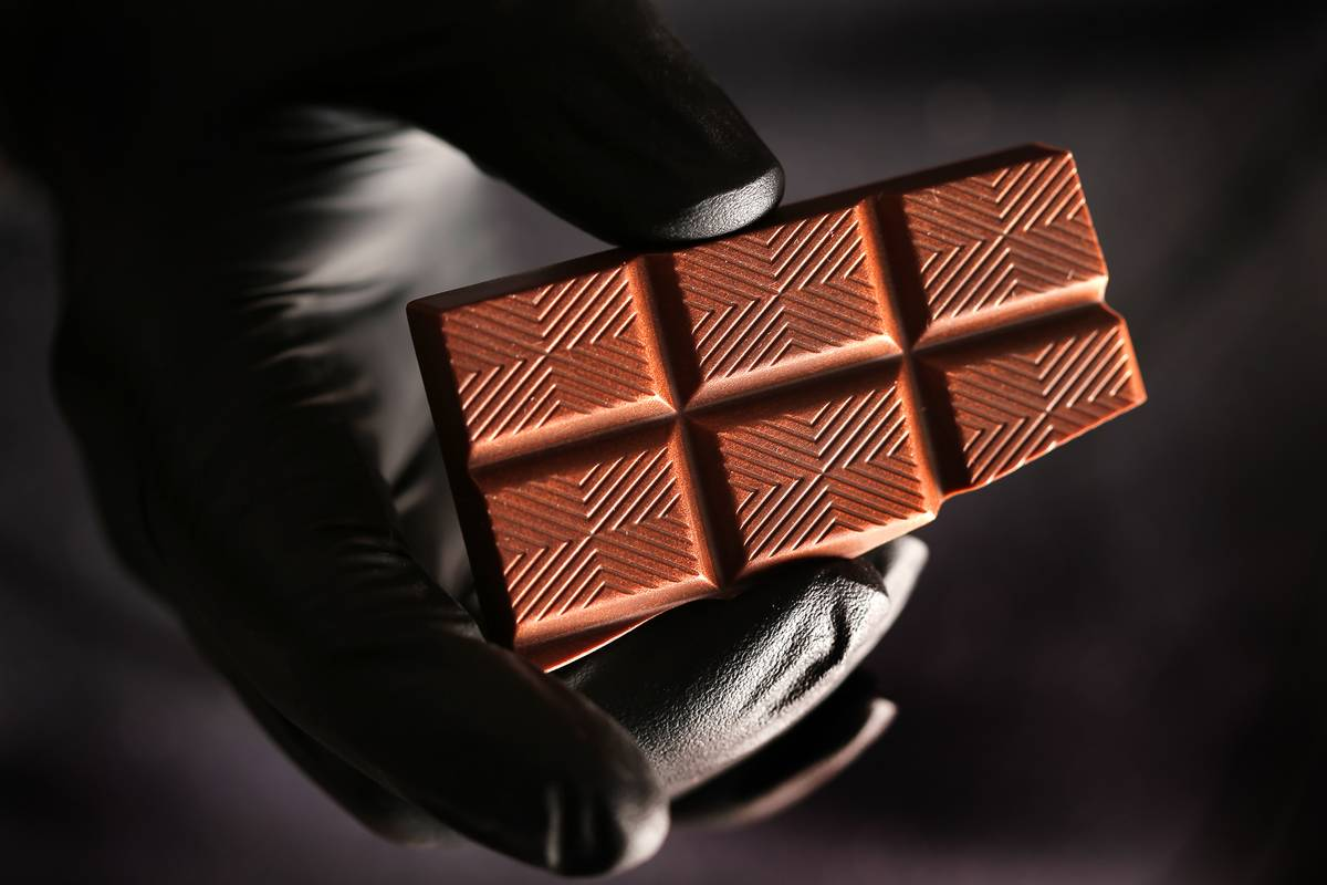 A gloved man holds a block of blended milk chocolate and dark chocolate.