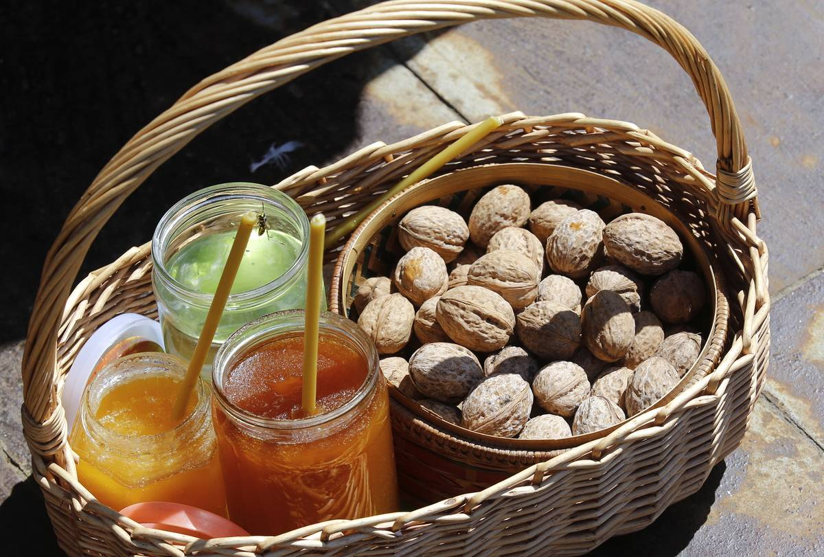 Walnuts sit in a basket with honey.