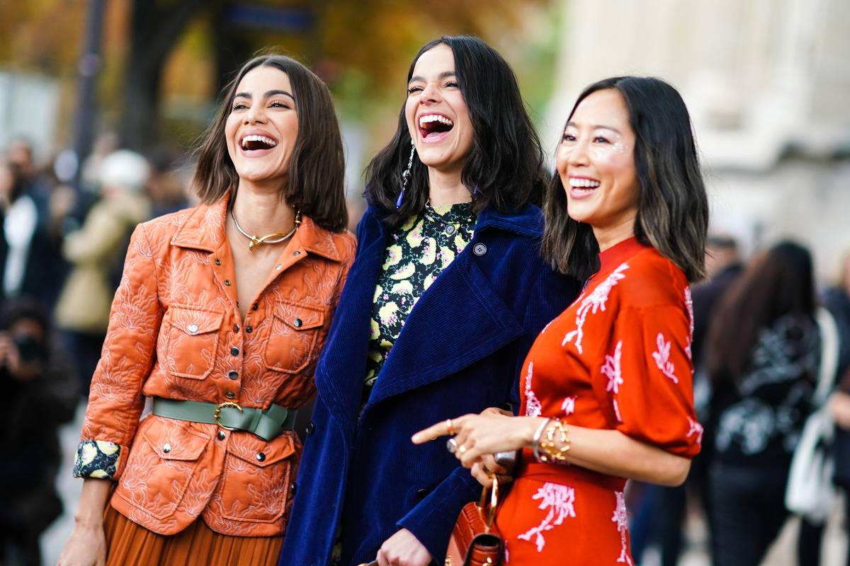 Mdels are Paris fashion week laugh while taking photos.