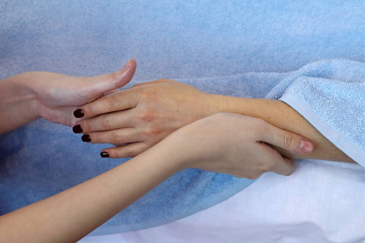 A woman receives a hand and wrist massage.