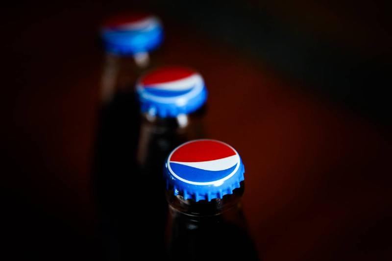 A photo shows the Pepsi logo on soda bottle caps.