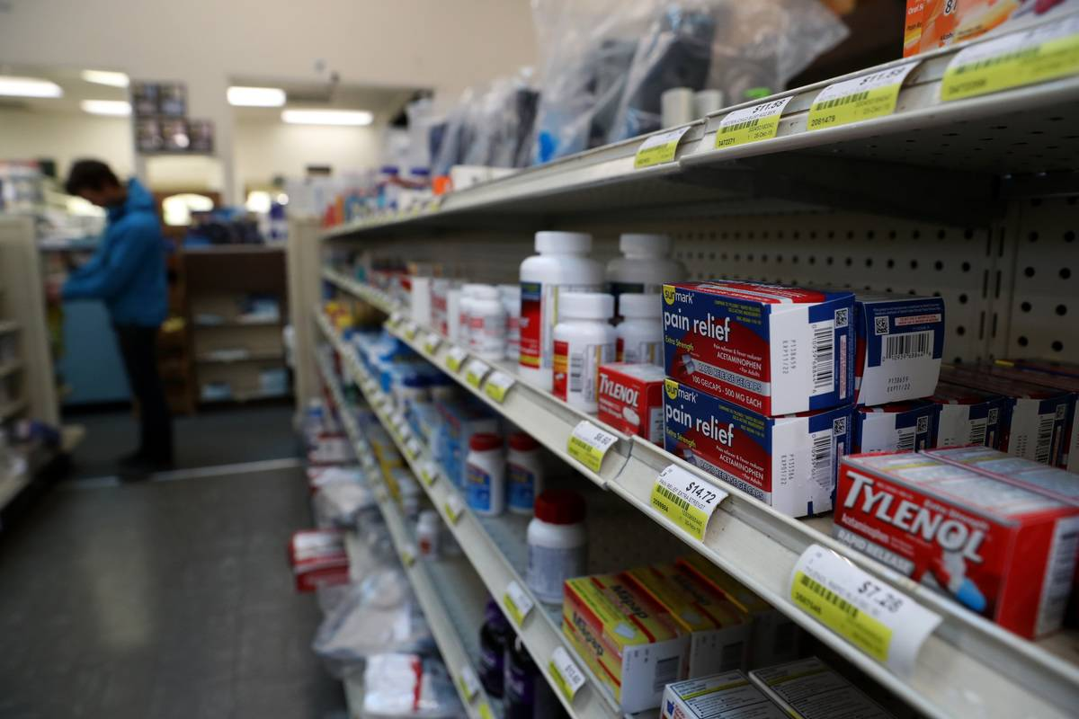 Acetaminophen are displayed on a shelf at a pharmacy.