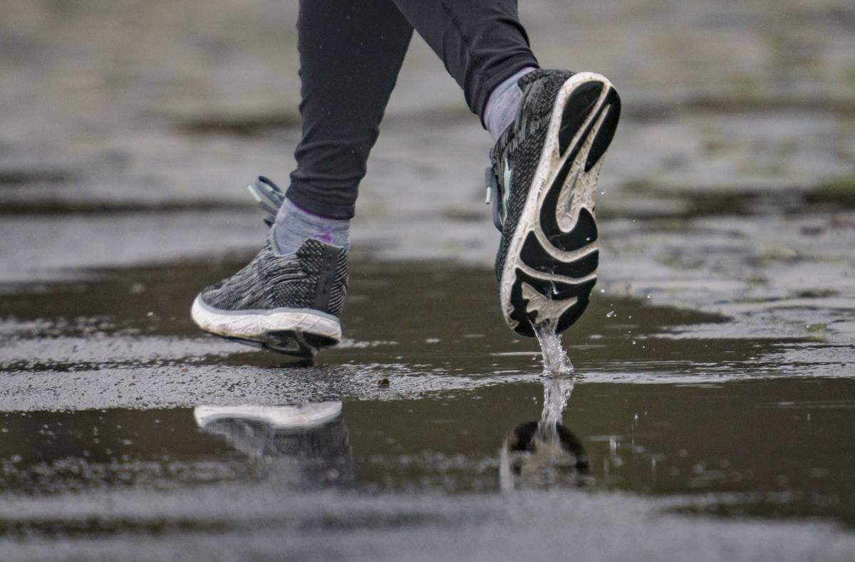 A close-up shows running shoes of a woman jogging in the rain.