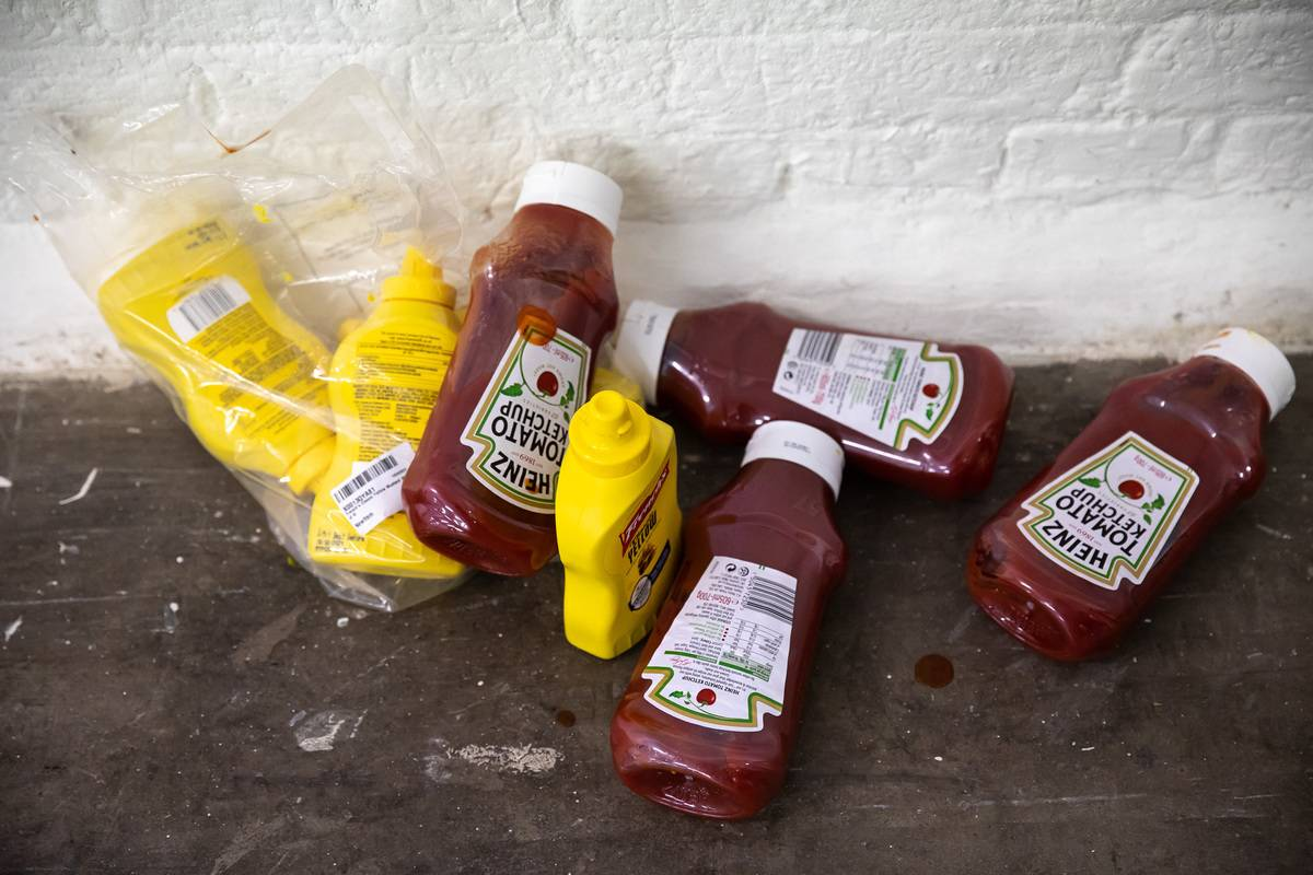 Discarded Ketchup and Mustard bottles sit on a concrete floor.