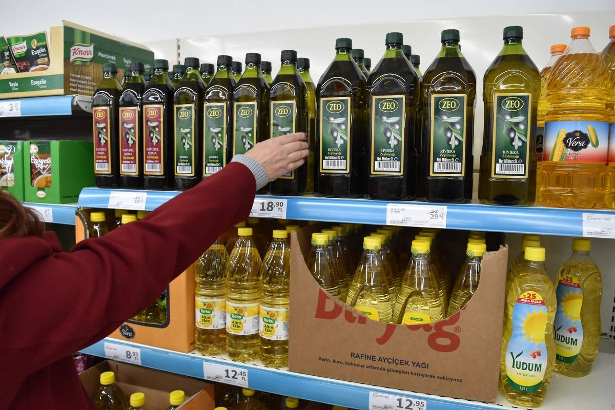 A shopper takes a bottle of olive oil at a small market.