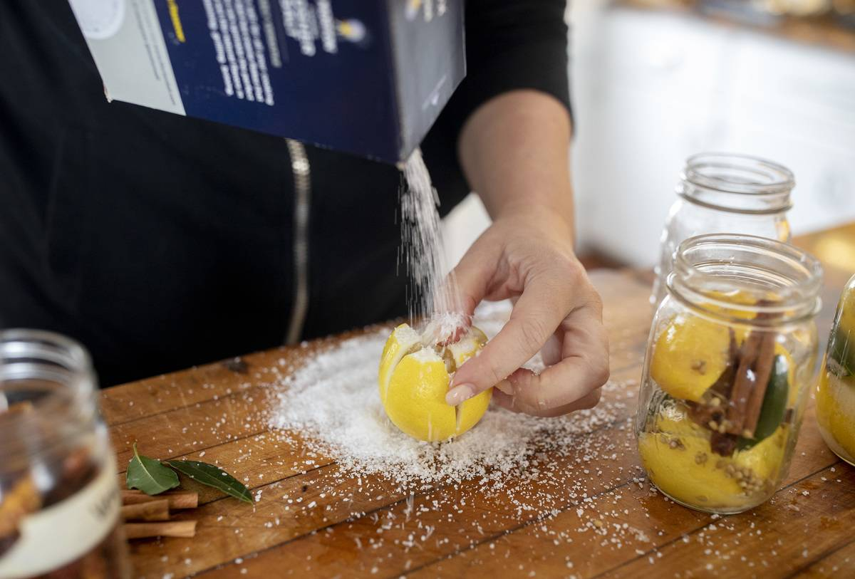 A chef generously salts a quartered lemon.