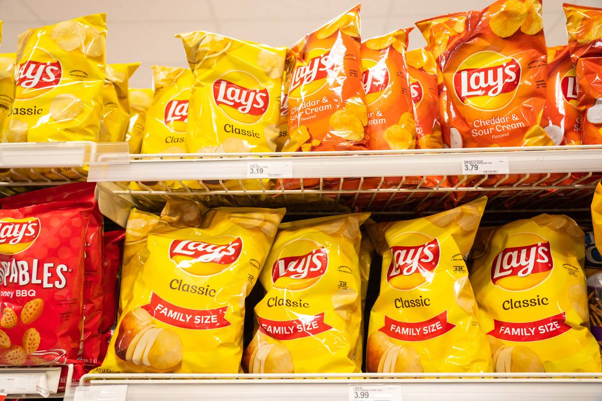 Bags of Lays potato chips sit on a grocery store shelf.