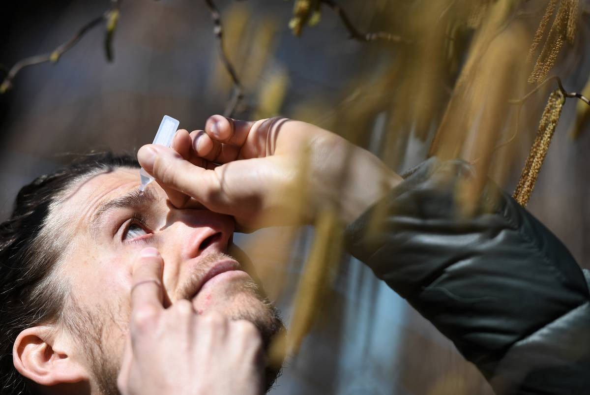 A man places eye drops into his eye for allergies.