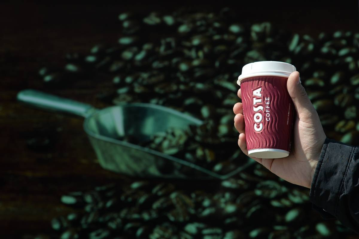 A man holds up a coffee cup in front of an image of coffee beans.
