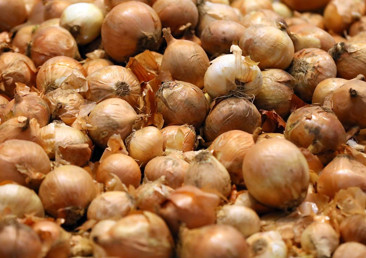 Whole white onions lie in a pile.
