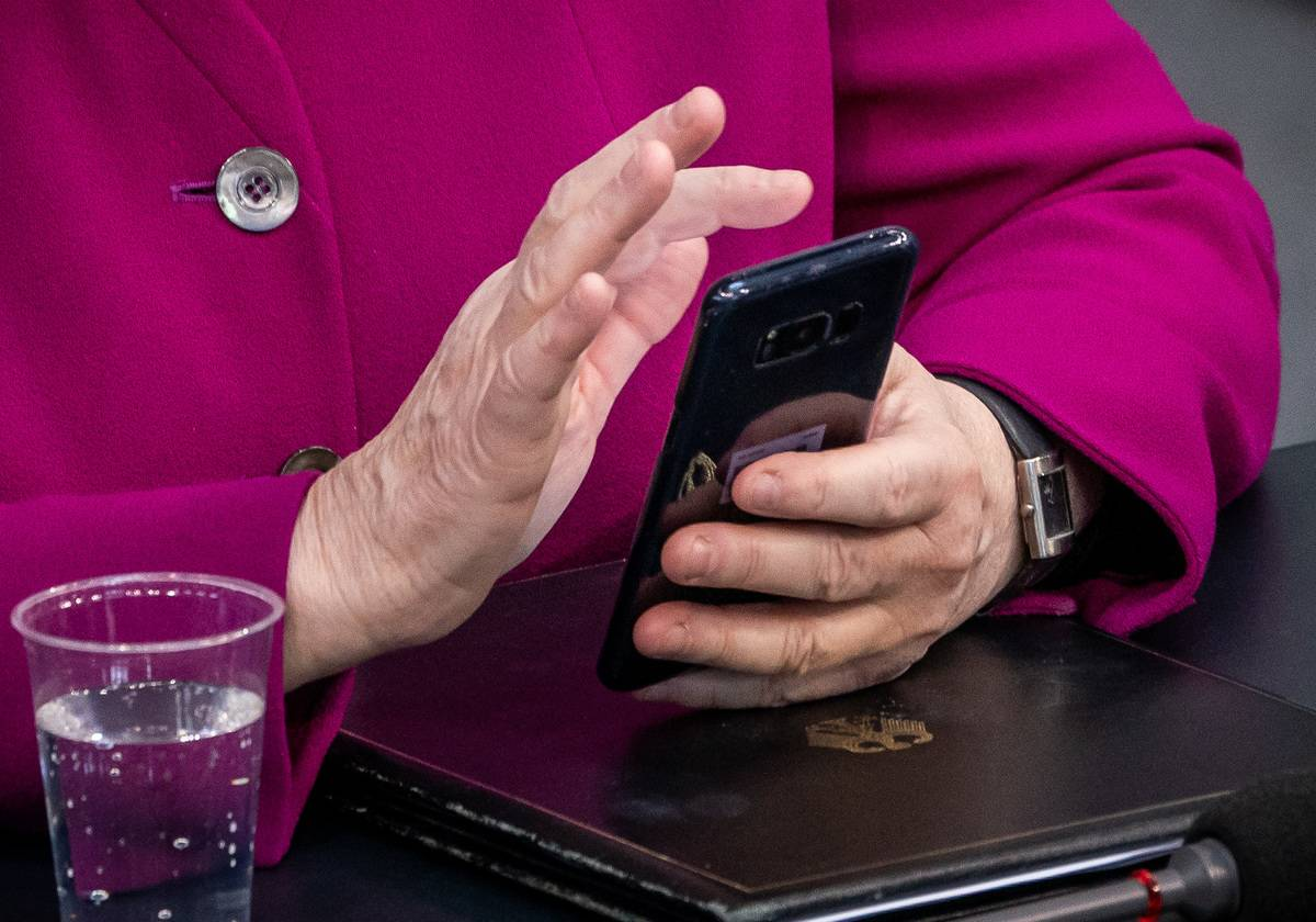 A woman scrolls through a smart phone.