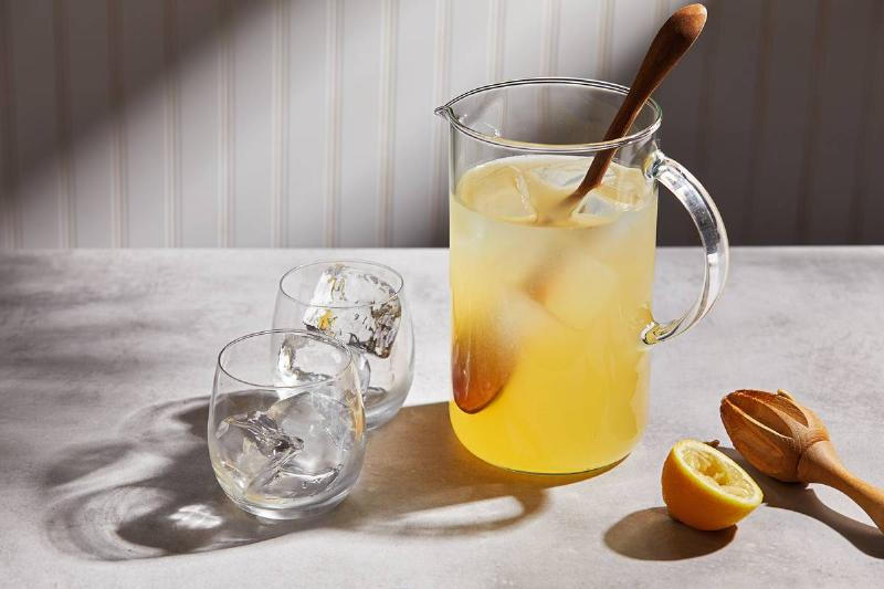 A pitcher holds fresh lemonade and a wooden spoon.