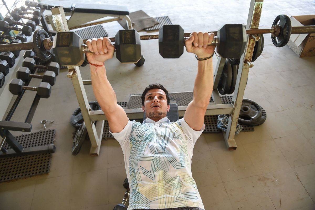 A man lifts weights at the gym.