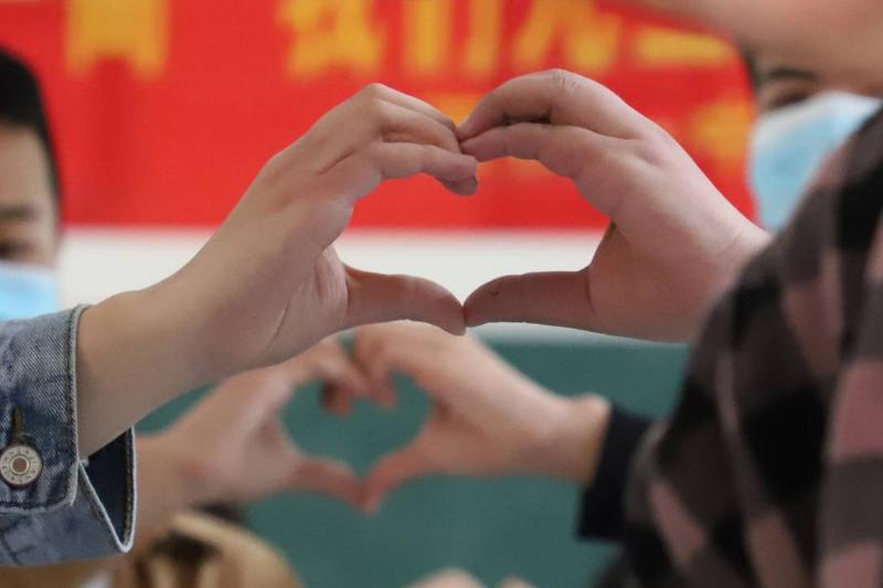Pairs of students hold their hands up together to form a heart.