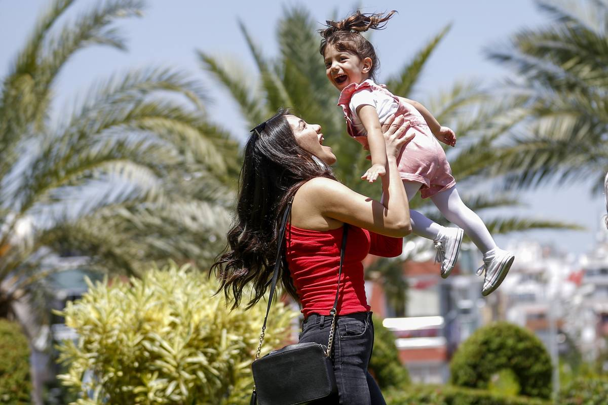 A mother lifts her daughter up while playing outside.