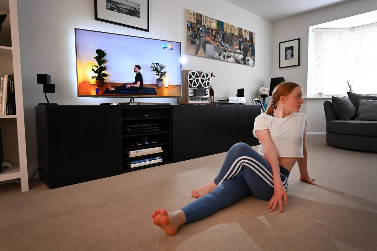 A woman follows a yoga tutorial on the TV.
