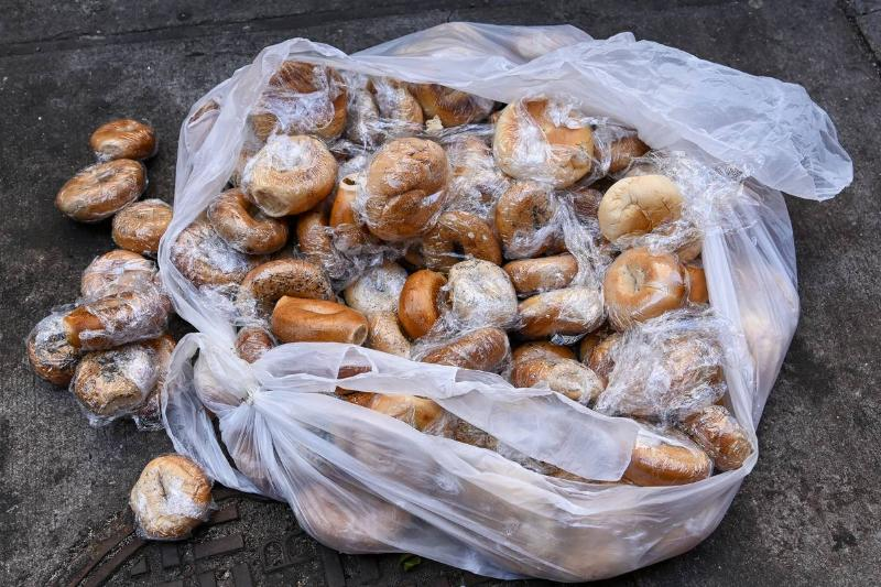A bag of bagels are on the street of New York.
