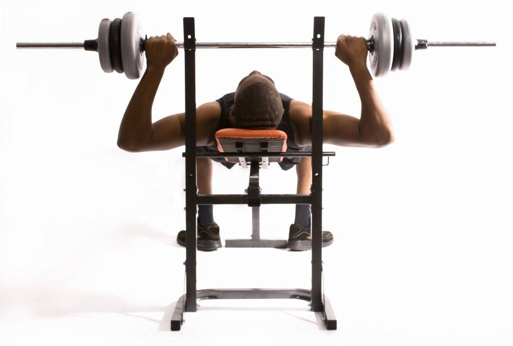 A man presses a barbell while laying back on a fitness bench.