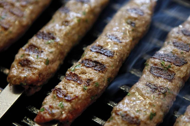Charred minced meat kebabs cook on a grill.