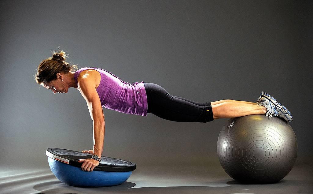 A woman balances on a bosu ball.