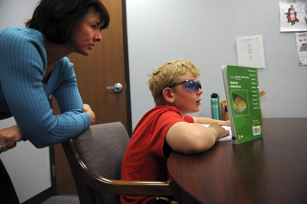 A nine-year-old works on cognitive skills by reading a textbook.