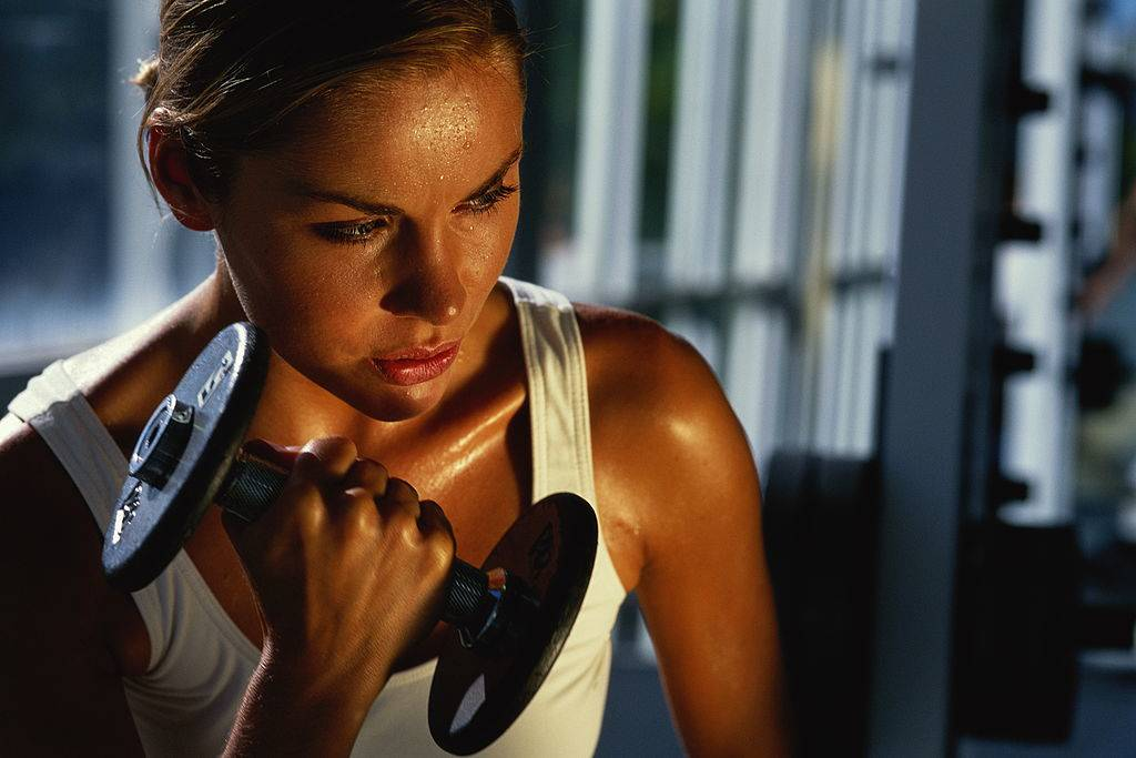 A woman curls a dumbbell.