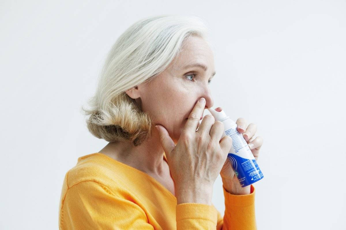 A woman sprays a decongestant into her nose.