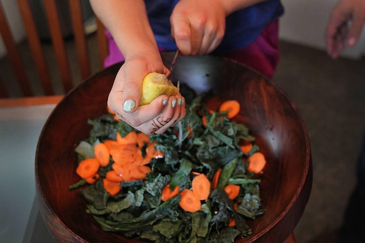 A girl squeezes lemon juice onto a kale slaw.