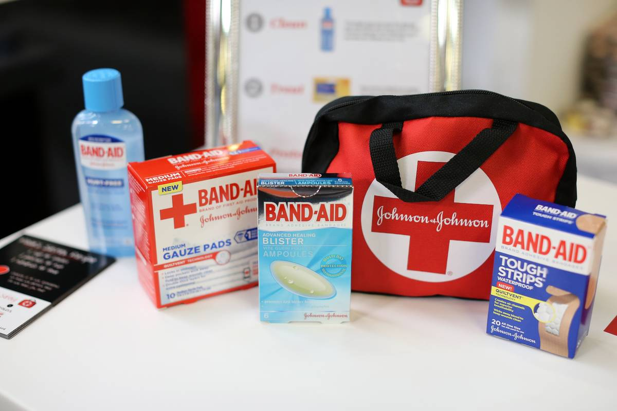 A first aid kit sits next to several different packages of Band-Aids.
