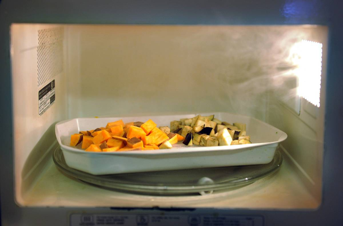 A microwave cooks a tray of sweet potatoes and eggplant.